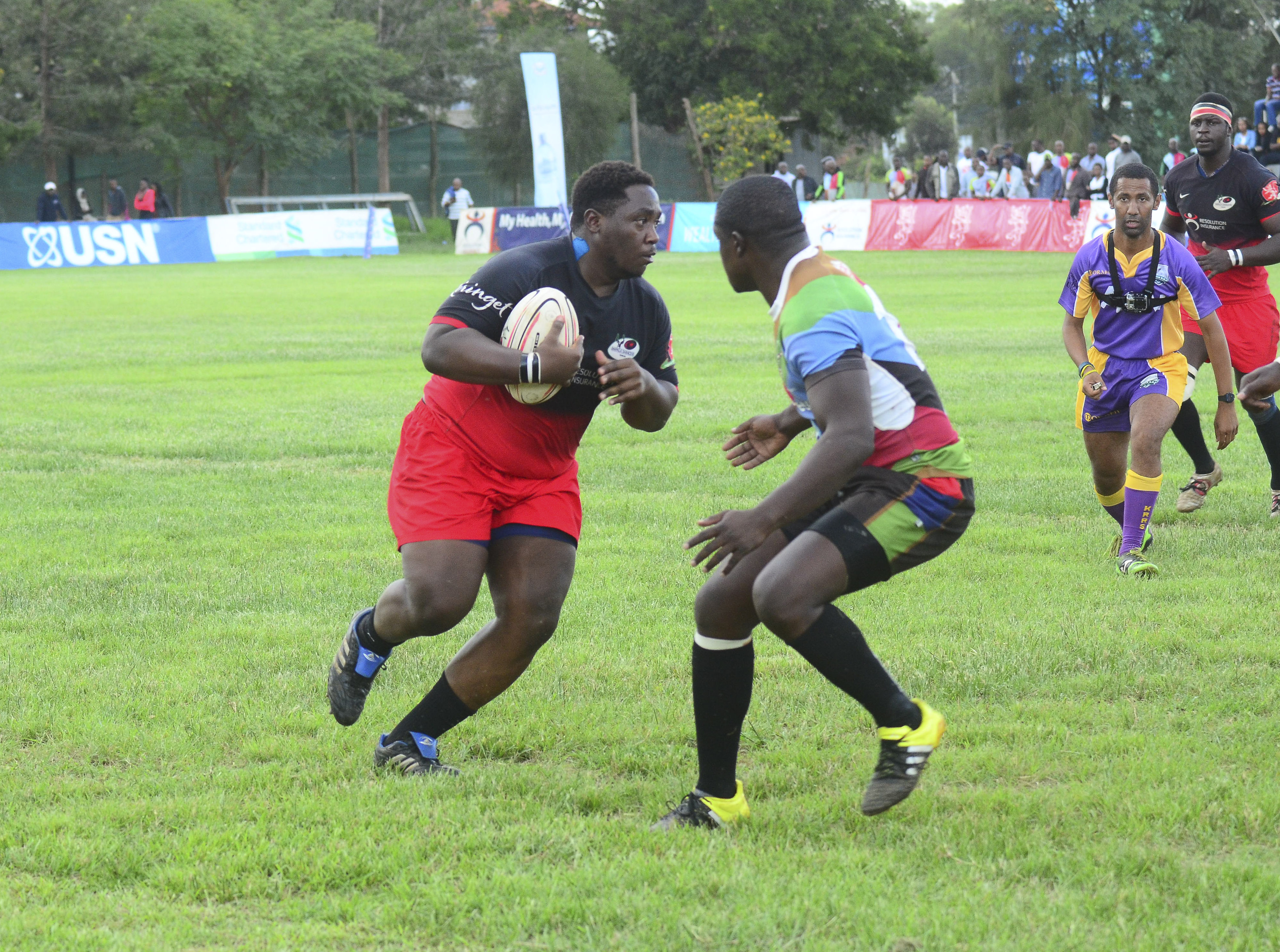 Impala prop-Meshack Tunechi attempts to go past Quins fly-half Isaac Adimo. onlooking is referee constant cap. Behind Cap is Impala lock Daniel Abok